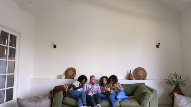 stockvideo's en b-roll-footage met ws family hanging out together on couch in living room - wide shot