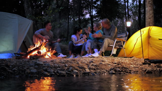 family, happiness, generation, vacation and people concept - the family is happy to outdoor camping activities. - guitar stock videos & royalty-free footage