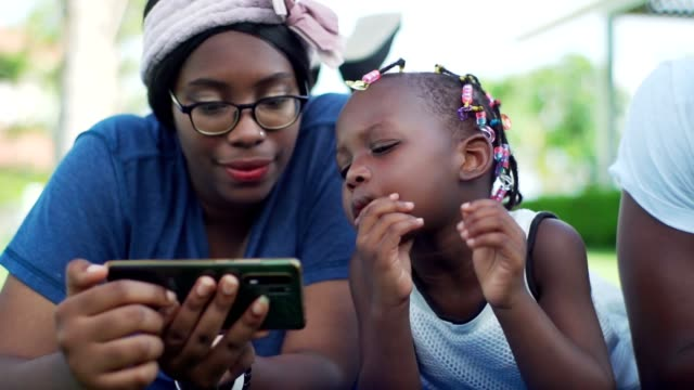 vidéos et rushes de famille heureuse père afro-américain mère et fille dans le parc. - 2 3 ans