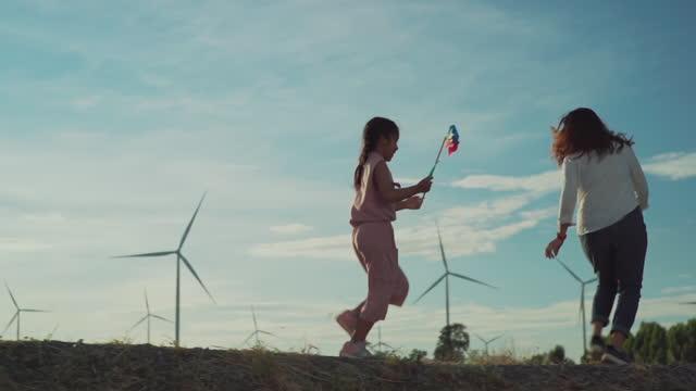 familie glücklich in windkraftanlagen bauernhof, zeitlupe. - fuel and power generation stock-videos und b-roll-filmmaterial