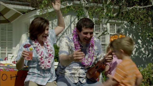 vídeos de stock, filmes e b-roll de a family has a hawaiian luau in their backyard. - ukulele