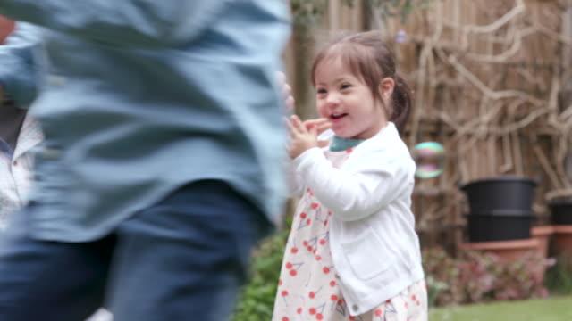 stockvideo's en b-roll-footage met een familie hebben plezier spelen in de tuin jagen bubbels - disability
