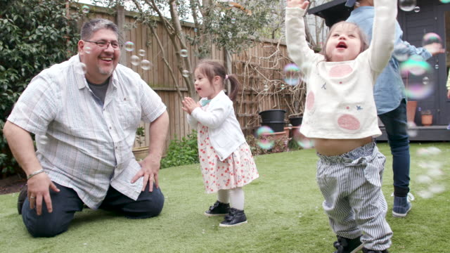 a family have fun playing in the garden chasing bubbles - preschool child stock videos & royalty-free footage