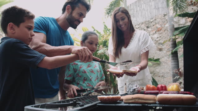 family having a barbecue near pool in holiday home - fleischzange stock-videos und b-roll-filmmaterial