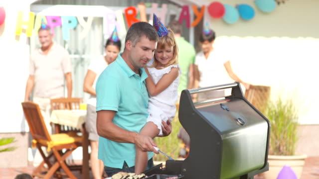 vidéos et rushes de hd: famille ayant une partie de barbecue - barbecue jardin