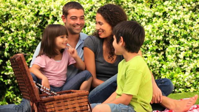 vidéos et rushes de family having a picnic in a park / cape town, western cape, south africa - prendre sur les genoux