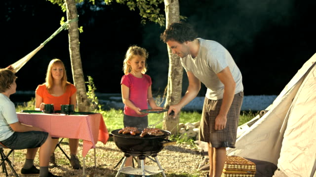 family having barbecue at campsite - passing giving stock videos & royalty-free footage