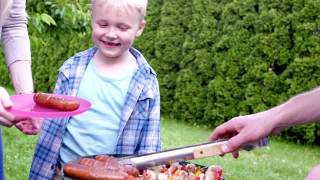 vidéos et rushes de famille ayant un barbecue - saucisse