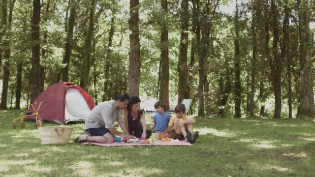 family having breakfast near tent in forest - picnic stock videos & royalty-free footage