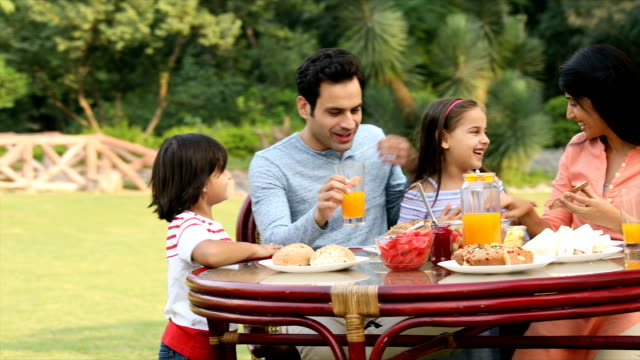 ms ds family having breakfast together in backyard / delhi, india - frühstück stock-videos und b-roll-filmmaterial