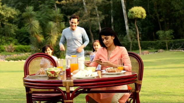 vídeos de stock e filmes b-roll de ms ds family having breakfast together in backyard while woman applying butter on bread / delhi, india - família jovem