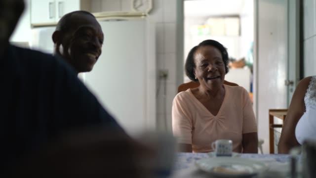 vidéos et rushes de famille ayant le café ensemble à la cuisine - coiffure afro