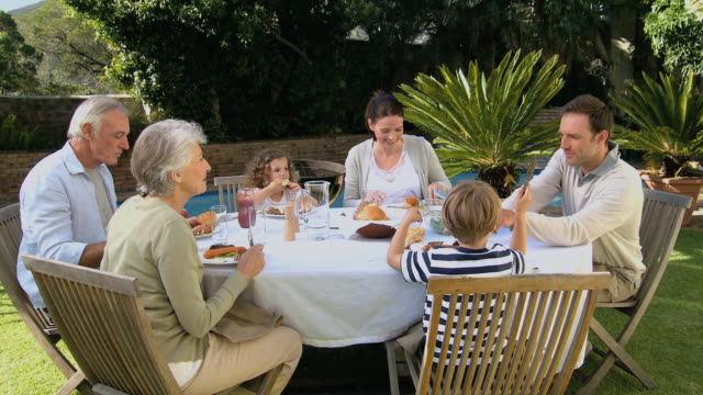 MS TD Family having dinner in garden near pool / Cape Town, Western Cape, South Africa