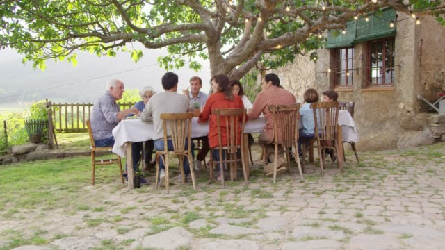 family having food at dining table outside house - lunch stock videos & royalty-free footage