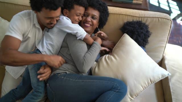 vídeos de stock, filmes e b-roll de família se divertindo e brigando de travesseiro juntos em casa - carinhoso