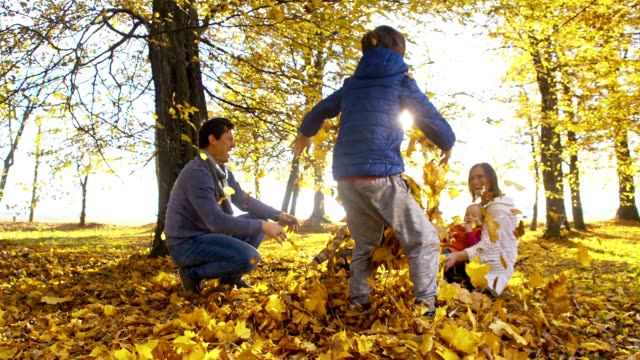slo mo family having fun in autumn park - family with three children stock videos & royalty-free footage