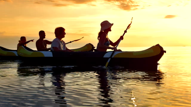 ts family having fun kayaking at sunset - canoe stock videos & royalty-free footage