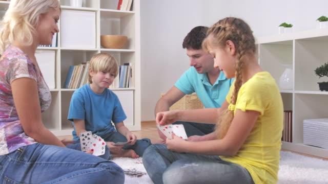 hd dolly: family having fun playing cards - kort bildbanksvideor och videomaterial från bakom kulisserna