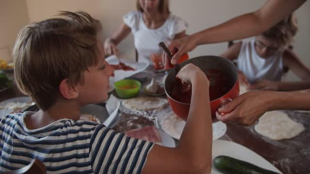family having fun preparing homemade pizza - tasting stock videos & royalty-free footage