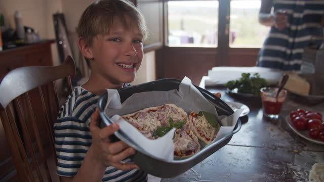 famiglia che si diverte a preparare la pizza fatta in casa - creazione video stock e b–roll