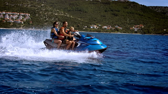 slo mo family having fun riding a jet boat - jet ski stock videos & royalty-free footage