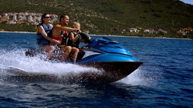 slo mo famiglia divertendosi guida su una moto d'acqua - acquascooter video stock e b–roll