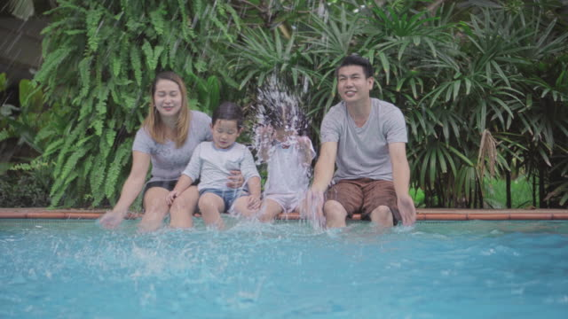 family having fun splashing each other on poolside,4k hand held - young family stock videos & royalty-free footage
