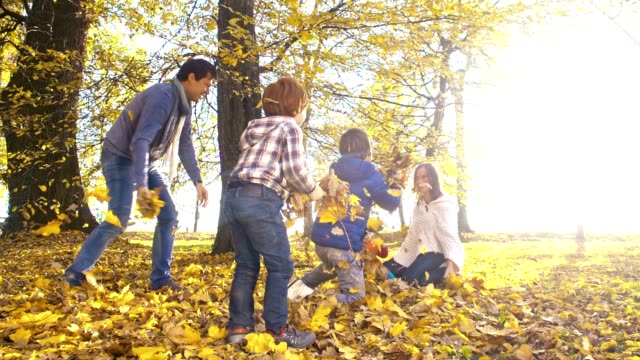 slo mo family having fun throwing autumn leaves - family with three children stock videos & royalty-free footage