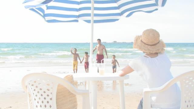 family having fun time on beach - 両親点の映像素材/bロール
