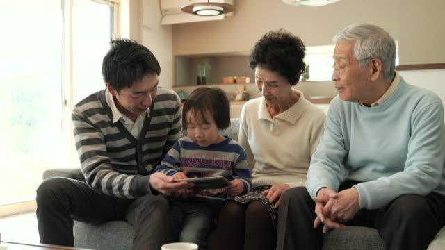 ご家族で楽しむデジタルタブレットを使用して、ご自宅で - 大家族点の映像素材/bロール