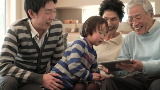 family having fun using a digital tablet together at home - desktop pc stock videos & royalty-free footage