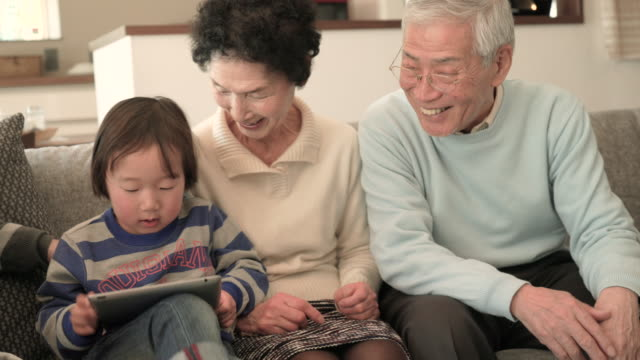 family having fun using a digital tablet together at home - japanese ethnicity stock videos & royalty-free footage