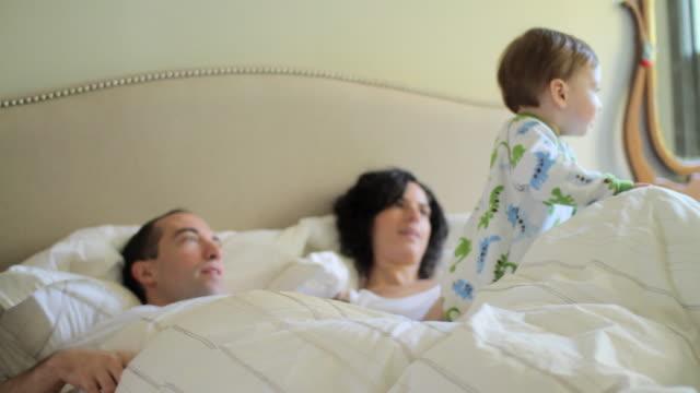 stockvideo's en b-roll-footage met family having lie in in bed - dubbel bed