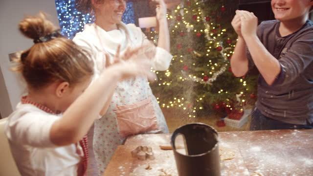 famiglia slo mo che si diverte molto mentre fanno biscotti di natale - messy video stock e b–roll