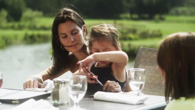 CU PAN Family having lunch in outdoor restaurant, girl (4-5) holding napkin / Squamish, British Columbia, Canada
