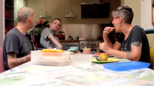 family having lunch with disabled son - documentary footage stock videos & royalty-free footage