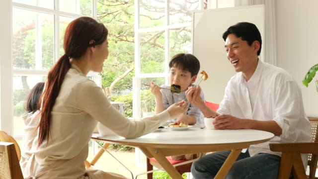 vídeos y material grabado en eventos de stock de family having meals on the dining table - comida coreana