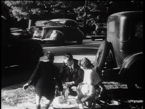 vídeos de stock e filmes b-roll de b/w 1939 family having picnic by roadside / documentary - 1939
