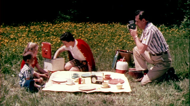 stockvideo's en b-roll-footage met 1958 montage cu zo ms family having picnic on meadow, man filming with super 8 camera / usa / audio - picknick