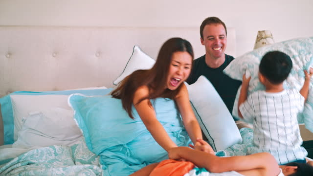 family having pillow fight in the bed - lying on back stock videos and b-roll footage
