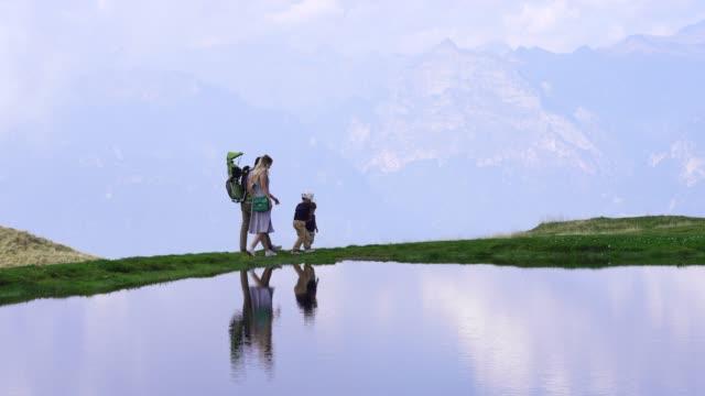 vidéos et rushes de famille de randonnée le long d'un lac de montagne aux reflets - alpes suisses