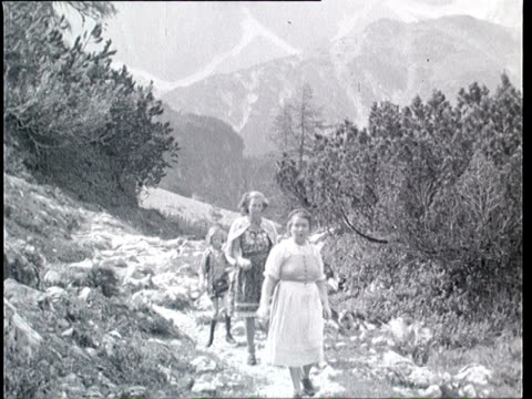 1937 b/w montage family hiking and having picnic in alpine landscape / tyrol, austria - オーストリア文化点の映像素材/bロール
