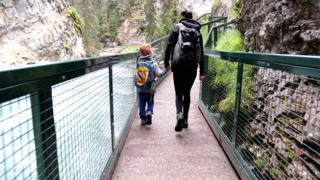 vídeos y material grabado en eventos de stock de senderismo familiar en johnston canyon, parque nacional banff, alberta, canadá - son