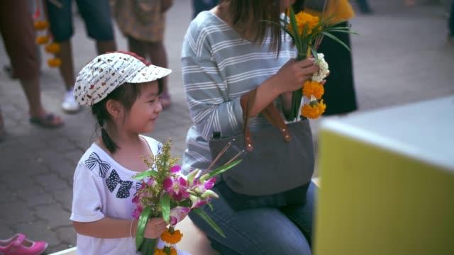 vídeos y material grabado en eventos de stock de familiar celebración quema incienso y rezando a buda en el templo - haz de luz
