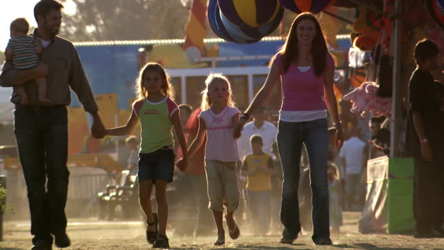 family holding hands at amusement park - 6 11 monate stock-videos und b-roll-filmmaterial