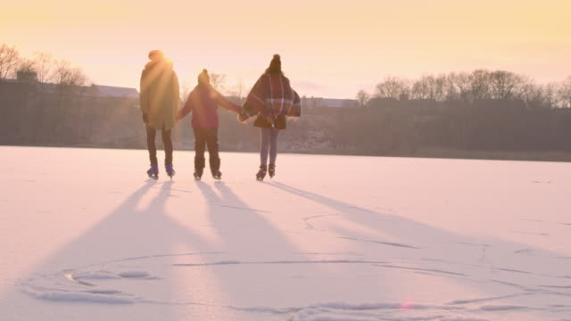 4k family holding hands ice skating on frozen lake, slow motion - two parents stock videos & royalty-free footage