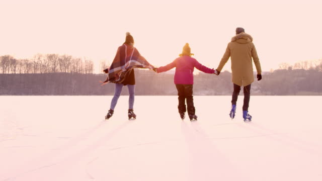 4K Family holding hands ice skating on frozen lake, slow motion