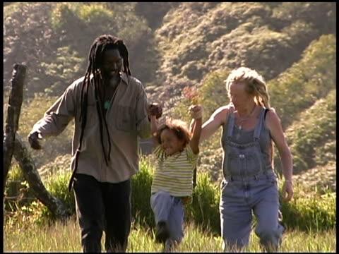 family holding hands in field - gemeinsam gehen stock-videos und b-roll-filmmaterial