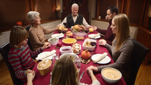 Family holding hands in prayer at Thanksgiving table
