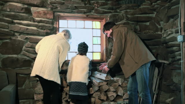Family holding logs in rustic house